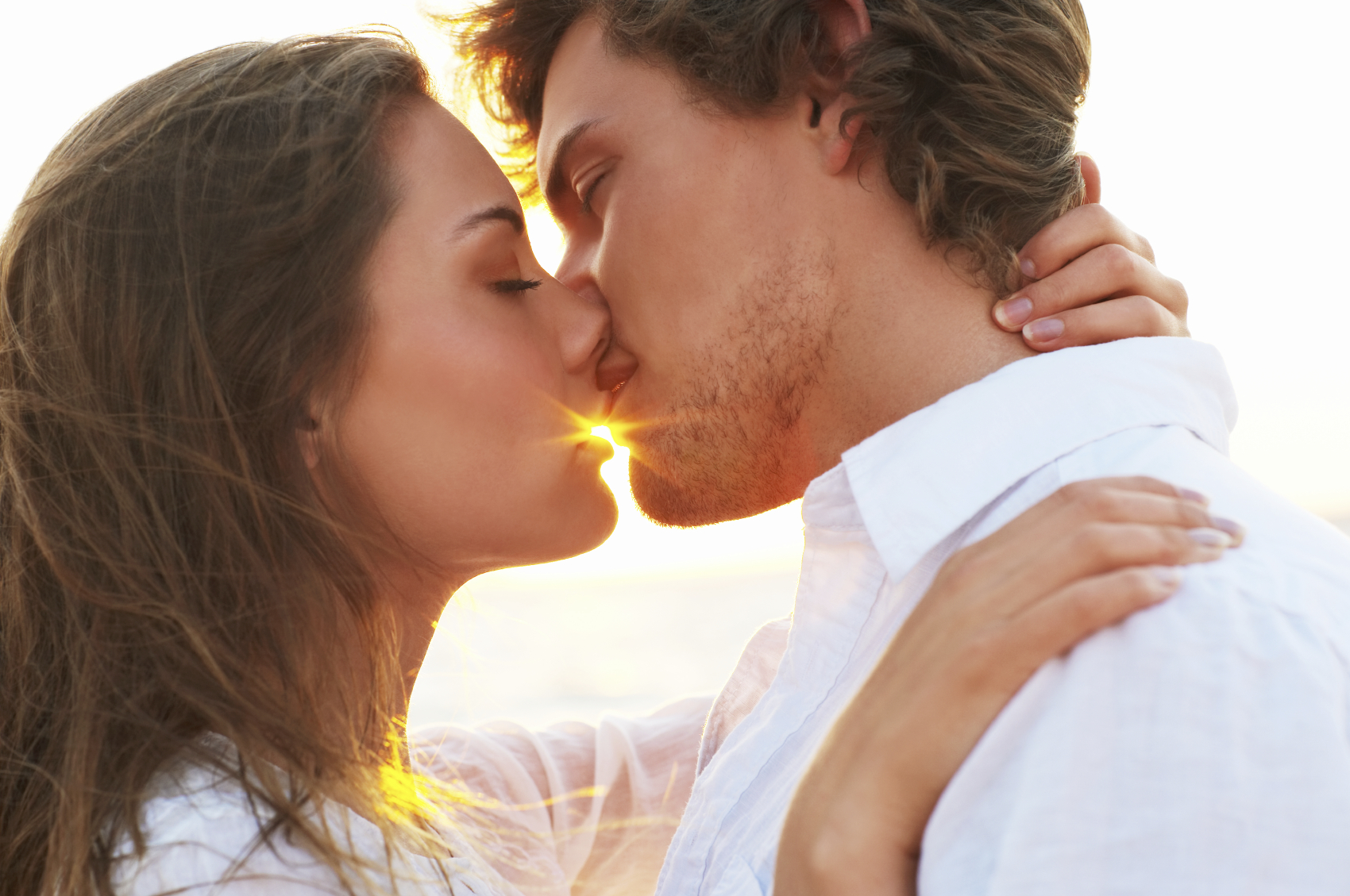 An attractive couple sharing a passionate kiss. Backlight portrait with flare from the sun.