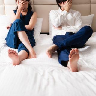 ベッド上悩む夫婦